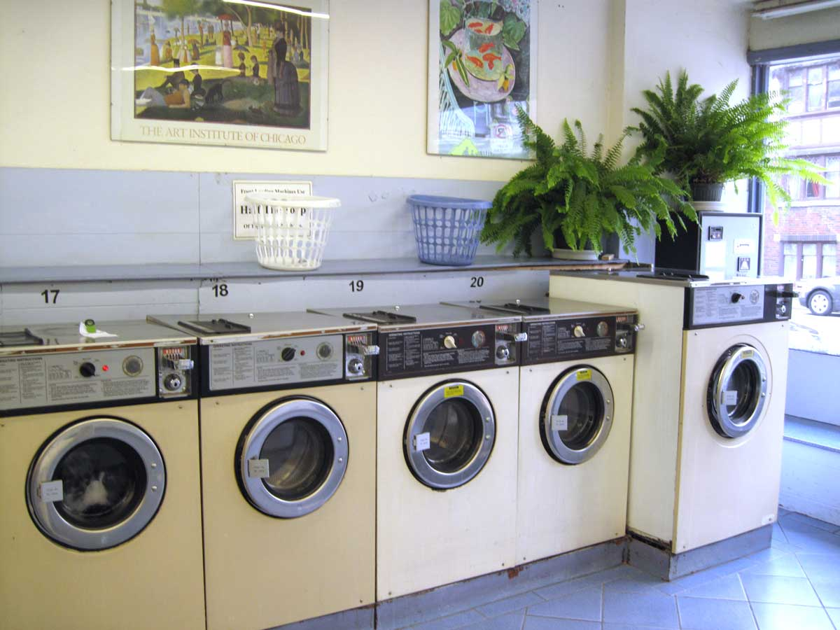Front-loading washing machines in laundromat with art on the wall